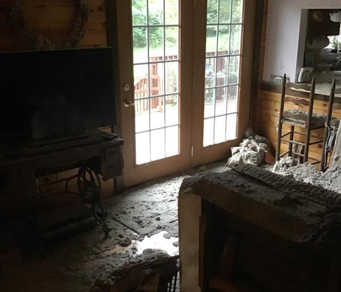 debris covers a living room after a roof collapsed